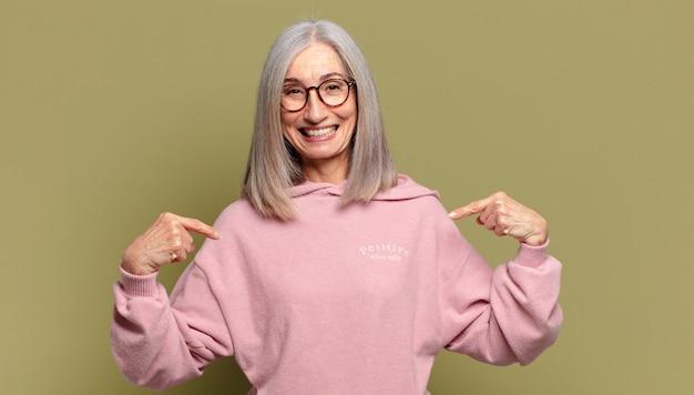 Starsza kobieta wyglądająca na dumną, pozytywną i swobodnie, wskazującą na klatkę piersiową obiema rękami
