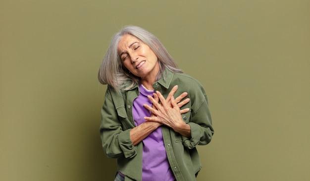 Starsza kobieta wyglądająca na smutną, zranioną i załamaną, trzymająca obie ręce blisko serca, płacząca i przygnębiona