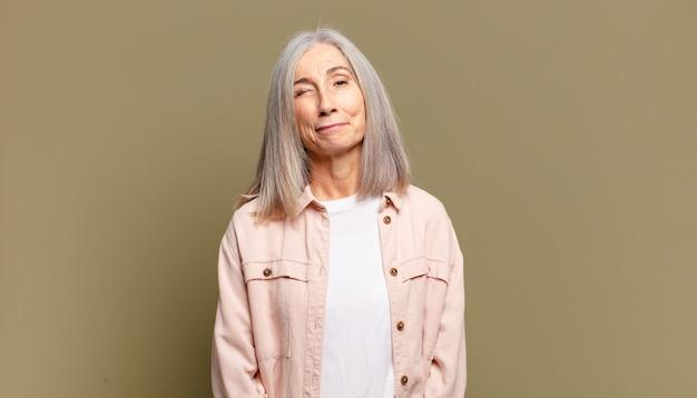 Starsza kobieta wyglądająca na szczęśliwą i przyjazną, uśmiechnięta i mrugająca do ciebie z pozytywnym nastawieniem