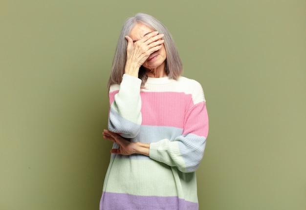 Starsza kobieta wyglądająca na zestresowaną, zawstydzoną lub zdenerwowaną, z bólem głowy, zakrywająca twarz ręką