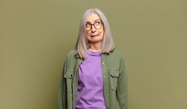 Starsza kobieta wyglądająca na zmartwioną, zestresowaną, niespokojną i przestraszoną, panikującą i zaciskającą zęby