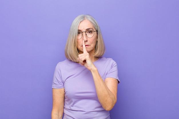 Starsza kobieta wyglądająca poważnie i skrzyżowana palcem na ustach, domagająca się ciszy lub spokoju, zachowująca tajemnicę