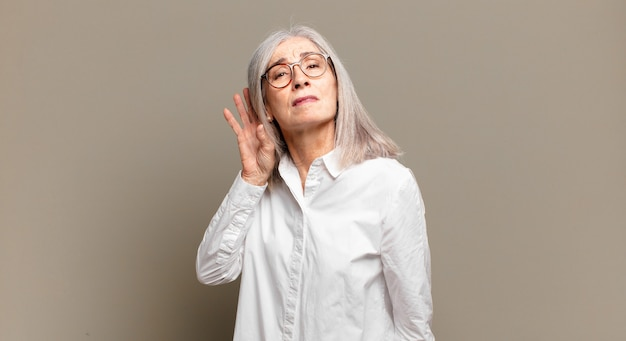 Starsza kobieta wyglądająca poważnie i zaciekawiona, słuchająca, próbująca usłyszeć tajną rozmowę lub plotkę, podsłuchująca