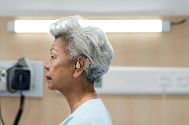 Starsza kobieta z aparatem słuchowym