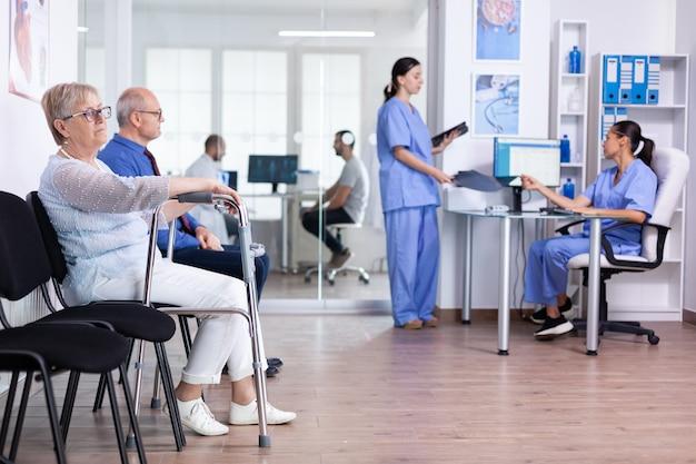 Starsza kobieta z balkonikiem w szpitalnej poczekalni na leczenie rehabilitacyjne