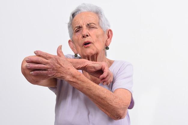 Starsza kobieta z bólem na łokciu na bielu