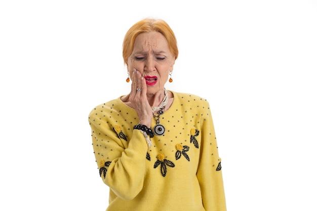Starsza kobieta z bólem zęba zdenerwowana kobieta dotykająca jej policzka uszkodzenie nerwu zębowego