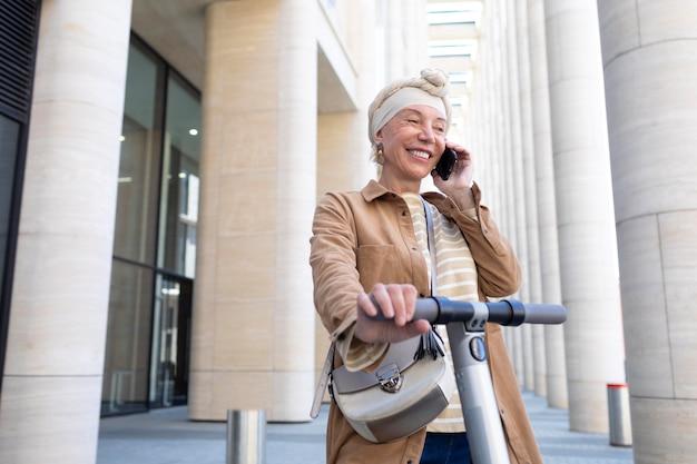 Starsza kobieta z elektryczną hulajnogą rozmawia przez telefon w mieście