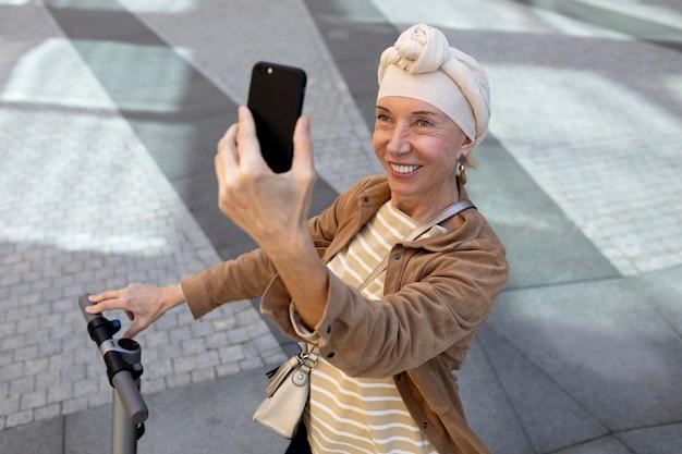 Starsza kobieta z elektryczną hulajnogą w mieście robi selfie