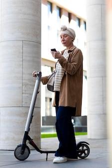 Starsza kobieta z elektryczną hulajnogą w mieście za pomocą smartfona
