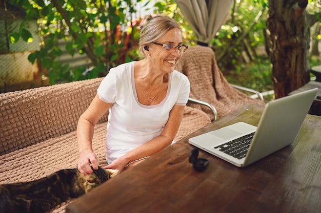 Starsza kobieta z kotem domowym używa słuchawek bezprzewodowych pracujących online z laptopem