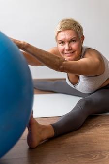 Starsza kobieta z krótkimi włosami robi sprawności