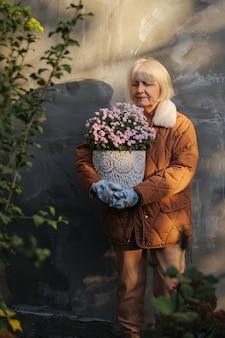 Starsza kobieta z kwiatami w słoneczny wiosenny dzień. starsza kobieta w odzieży wierzchniej niosąca kwiaty doniczkowe
