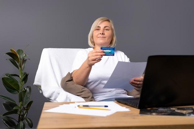Starsza kobieta z laptopem i kartą bankową płaci za dostawę i pozuje na krześle