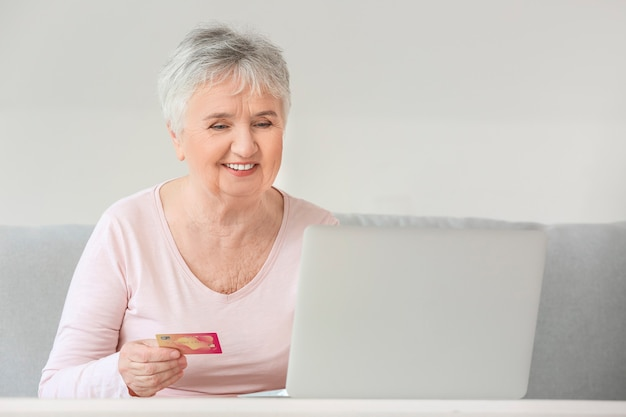 Starsza kobieta z laptopem i kartą kredytową w domu