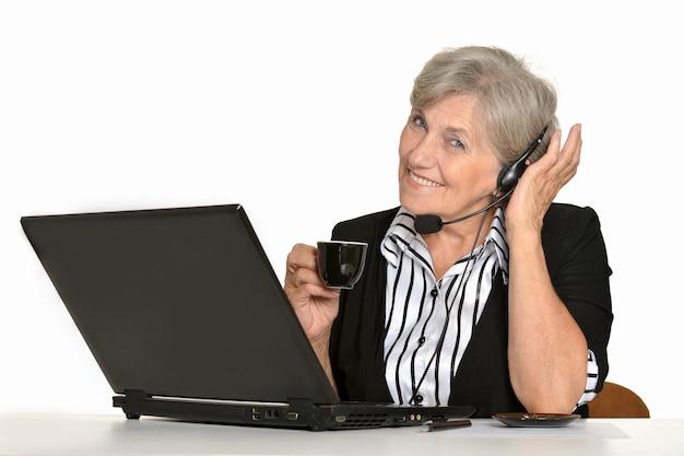 Starsza kobieta z laptopem na białym tle