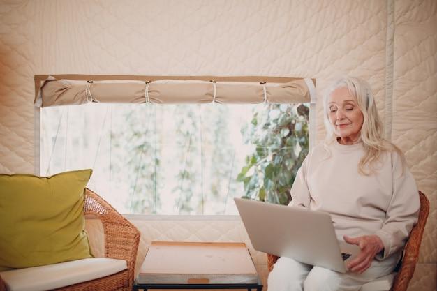 Starsza kobieta z laptopem relaksując się w glampingowym namiocie kempingowym nowoczesnej koncepcji stylu życia wakacje