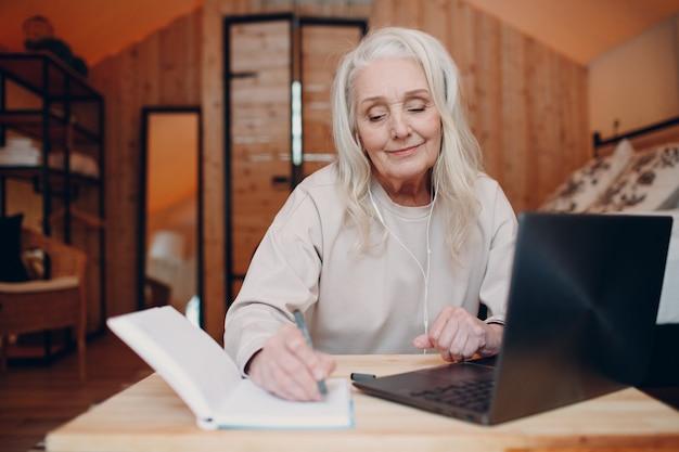 Starsza kobieta z laptopem siedzi przy stole i rozmawia w glampingowym namiocie kempingowym koncepcja nowoczesnego stylu życia wakacyjnego