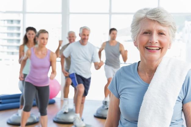 Starsza kobieta z ludźmi ćwiczy w sprawności fizycznej studiu