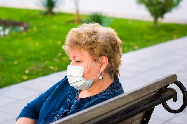 Starsza kobieta z ochronną maską medyczną w parku na ławce osoby w podeszłym wieku zagrożone koronawirusem covid-19