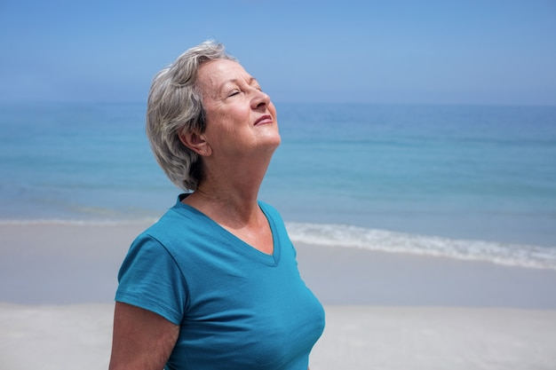 Starsza kobieta z oczami zamykającymi na plaży
