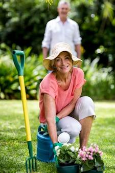 Starsza kobieta z ogrodnictwa wyposażeniem w jardzie
