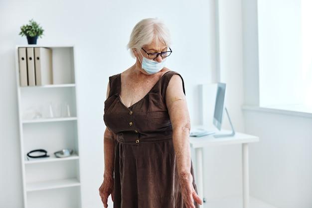 Starsza kobieta z plastrem maski medycznej na ramieniu paszportu szczepionki