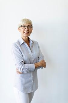 Starsza kobieta z rękami skrzyżowanymi stojąc przy ścianie w biurze