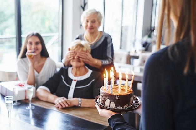 Starsza kobieta z rodziną i przyjaciółmi świętuje urodziny w pomieszczeniu.