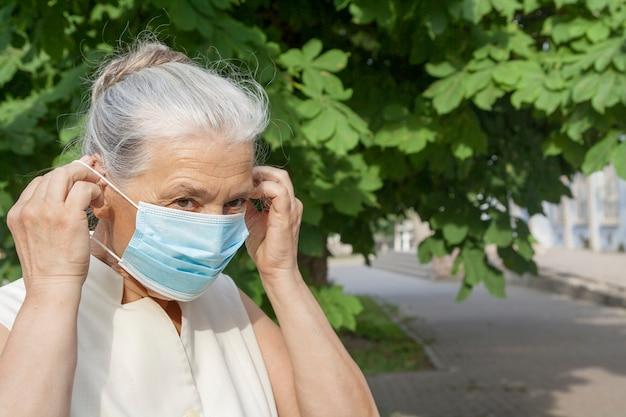 Starsza kobieta z siwe włosy ubrania medyczne maski na zewnątrz.