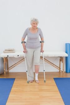Starsza kobieta z szczudłami w szpitalnym gym