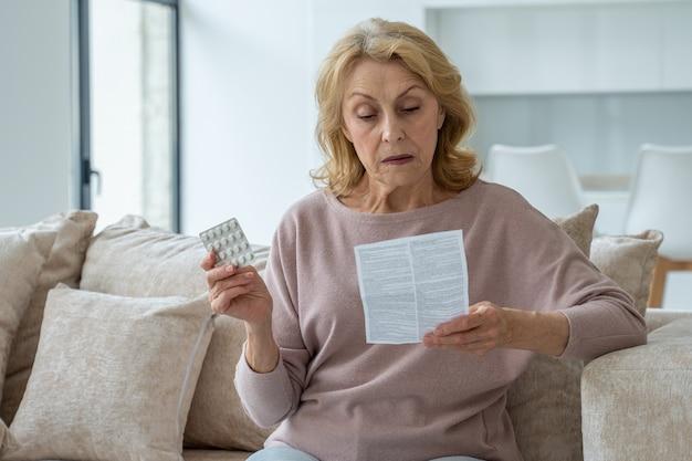 Starsza kobieta z tabletkami czyta instrukcję w domu siedząc na kanapie