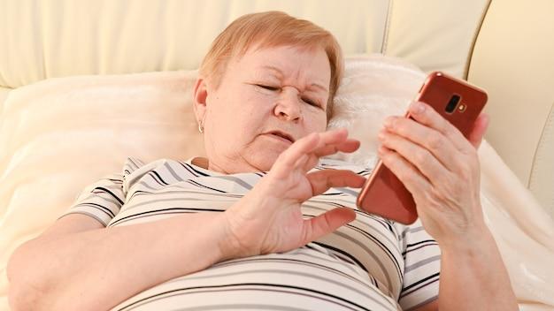 Starsza kobieta z telefonem komórkowym w domu.