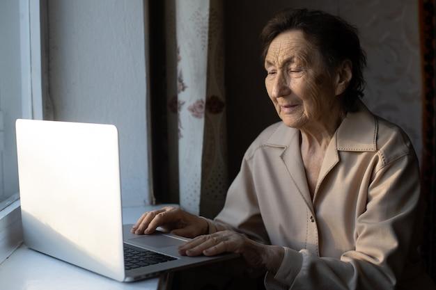 Starsza kobieta za pomocą laptopa