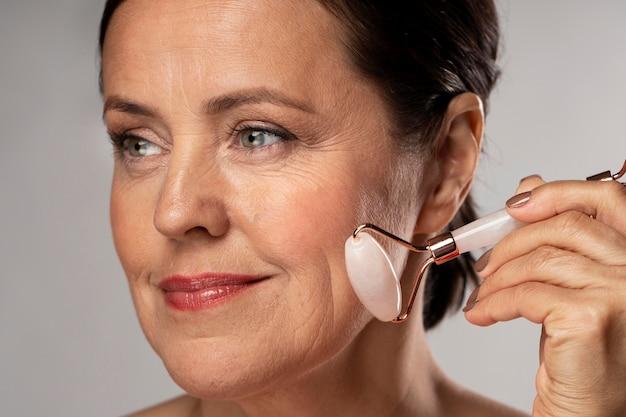 Starsza kobieta za pomocą wałka do twarzy z różowego kwarcu na skórze