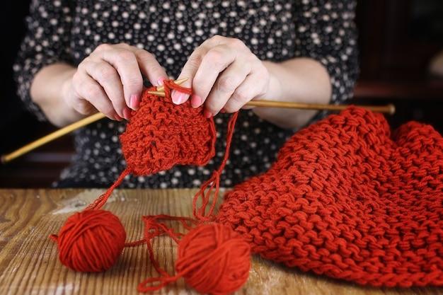 Starsza kobieta zajmuje się robieniem na drutach ciepłych swetrów dla wnuków
