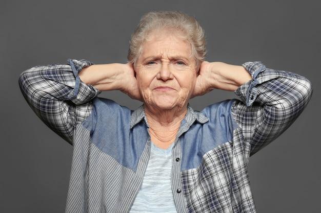 Starsza kobieta zakrywa uszy na szarej powierzchni
