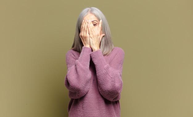 Starsza kobieta zakrywająca twarz rękami, zerkająca między palcami z zaskoczonym wyrazem i patrząc w bok