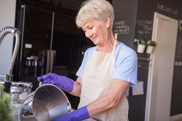 Starsza kobieta zmywa naczynia