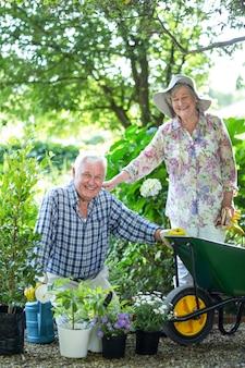 Starsza kobiety pozycja mężem z doniczkowymi roślinami