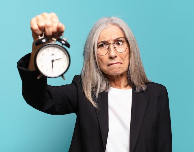 Starsza ładna bizneswoman z budzikiem
