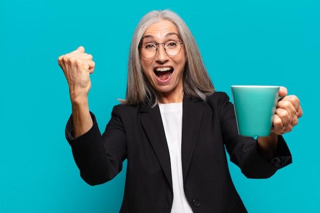 Starsza ładna bizneswoman z filiżanką kawy