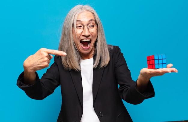 Starsza ładna bizneswoman z wyzwaniem inteligencji rozwiązującym koncepcję problemu