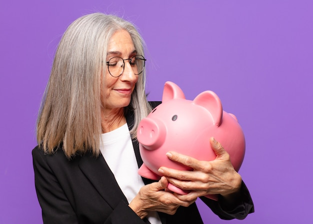 Starsza ładna bizneswoman ze skarbonką