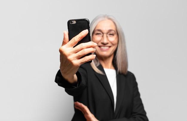 Starsza ładna bizneswoman ze smartfonem