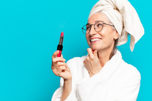 Starsza ładna kobieta po prysznicu, makijaż i noszenie szlafroka
