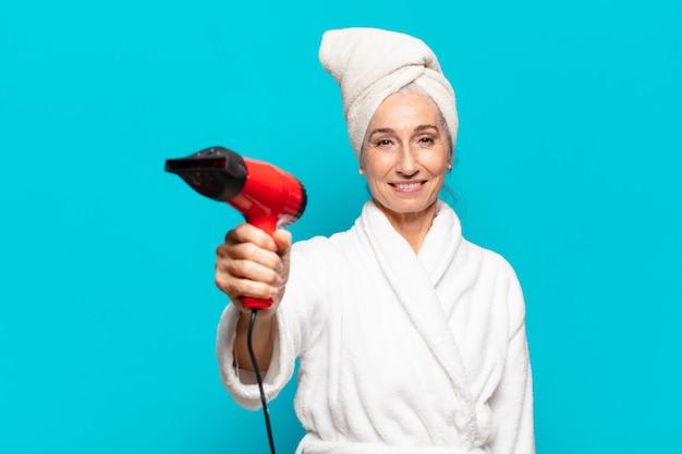 Starsza ładna kobieta po prysznicu nosi koncepcję suszarki do włosów w szlafroku