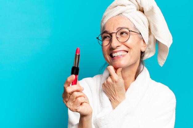 Starsza ładna kobieta po prysznicu robienie makijażu i noszenie szlafroka