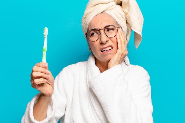 Starsza ładna kobieta po prysznicu, ubrana w szlafrok i ze szczoteczką do zębów
