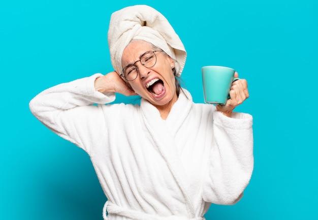 Starsza ładna kobieta ubrana w szlafrok i pijąca kawę